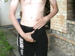 Skinny twink is undressing and posing at the backyard