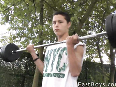 Cute and tender gay guy is lifting weights outdoors