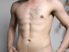 Charming sexy guy is lifting dumbbells in front of his camera